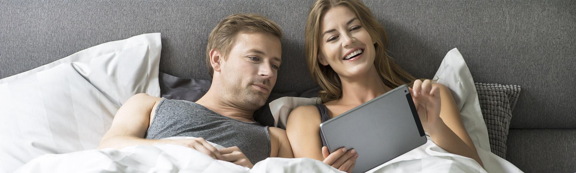ベッドで微笑む男女の写真